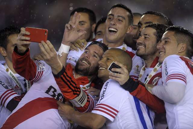 TOPSHOTS Argentinian River Plate Fernando Cavenaghi (C) makes a selfie with his teammates after winning the Libertadores Cup second leg final match against Mexican Tigres by 3-0 and becoming champions at Americo Vespucio stadium, in Buenos Aires, on August 5, 2015. AFP PHOTO/Alejandro Pagni