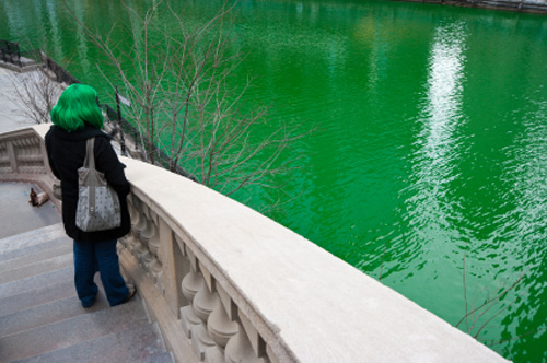 Girl with green wig watching dyed Chicago River during St. Patrick's Day.